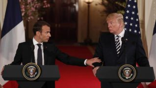 French President Macron reaches out to U.S. President Trump during their joint news conference at the White House in Washington